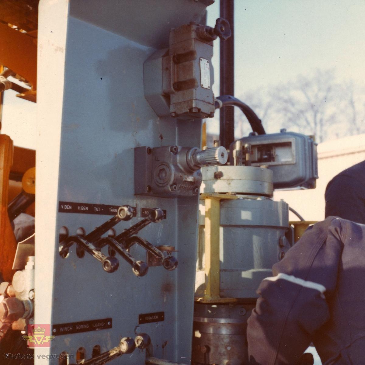 """Kurs i bruk av """"Hydroriggen"""" (grunnboringstraktor) utenfor Veglaboratoriet i Oslo feb. 1970.   Utviklingen av """"Hydroriggen""""på slutten av 1960-t revolusjonerte grunnboringsarbeidet. Det manuelle arbeidet ble redusert, den var lettere å flytte og hadde større kapasitet og evne til nedtrengning. En ny metode kalt dreietrykksondering ble tatt i bruk: Man målte hvor mye kraft som måtte til for å trykke borstengene ned i bakken med konstant hastighet og rotasjon. Riggen kunne også benyttes til andre sonderingsmetoder, prøvetaking og vingeboring. Hydroriggen hadde begrenset framkommelighet tiltross for at den var utstyrt med halvbelter.   Kilde: Rapport nr: 2550, Teknologiavdelingen SVV: """"Grunnboringsutstyr 1960-2000"""""""