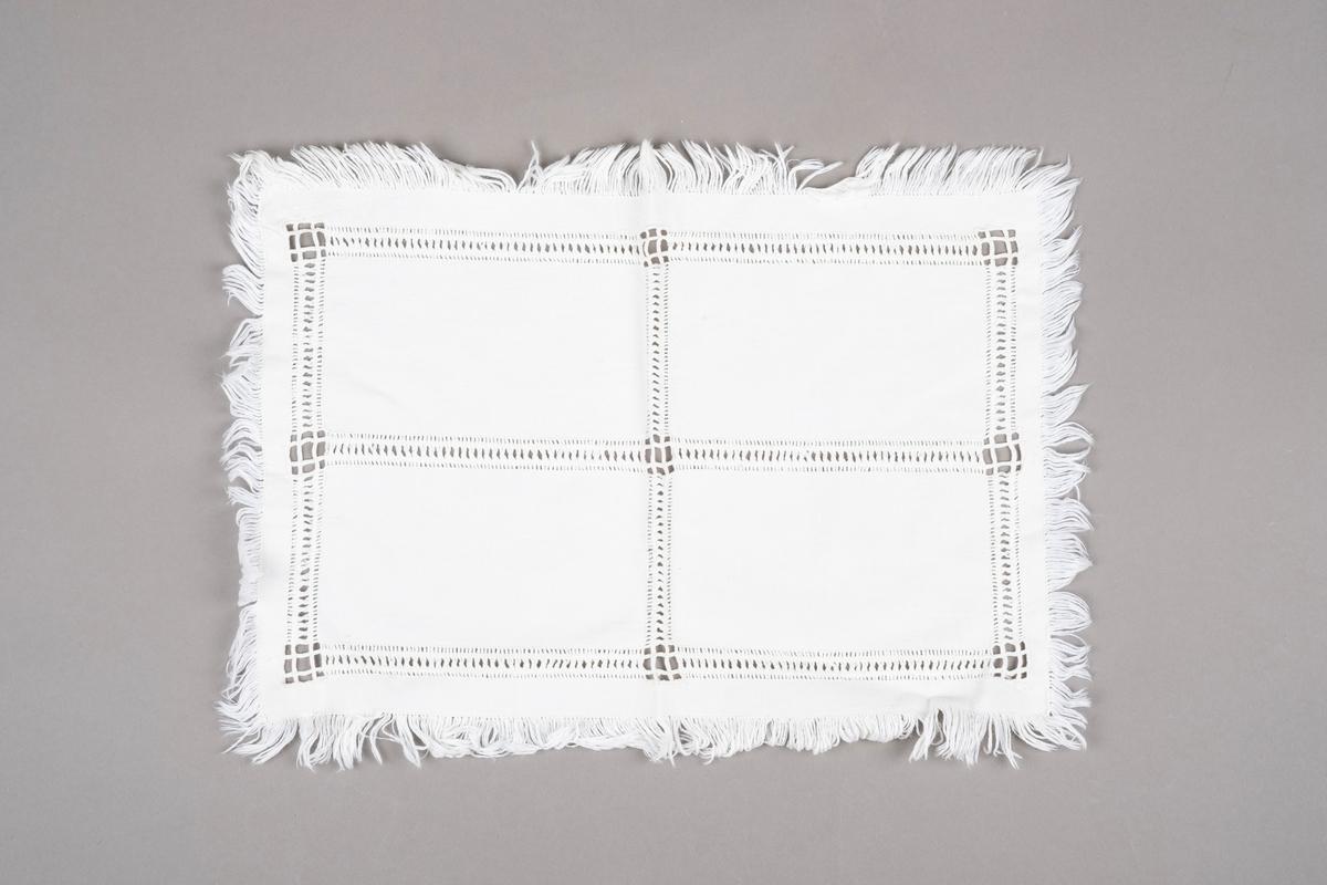 Et rektangulært bordduk med frynsekanter og hull- og sammentrekkssøm.