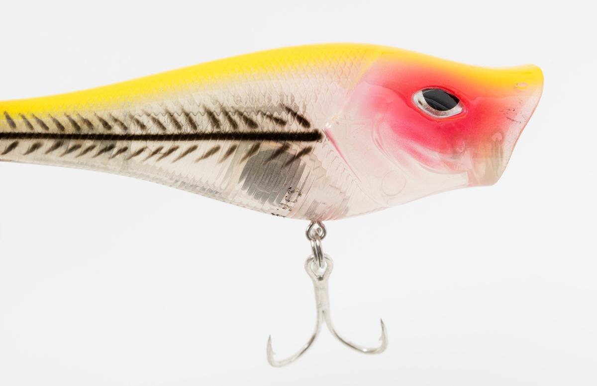 """Kunstig agn, spinnagn, wobbler , av typen Abu Garcia Rocket Popper 90. Dette kunstige agnet er en fiskeimitasjon i gjennomsiktig, delvis bemalt plast i gult, rødt og svart . Den hule """"slukkroppen"""" rommer 1 stor og 3 små blykuler. De små blykulene beveger seg og avgir en raslende lyd.    Spinnagnet er utstyrt med to treblekroker, en på undersiden og en i halen. Treblekorken i halen har hvite fjær som er surret fast til krokskaftet med rød tråd. Begge trippelkrokene er festet til wobbleren med splittringer."""