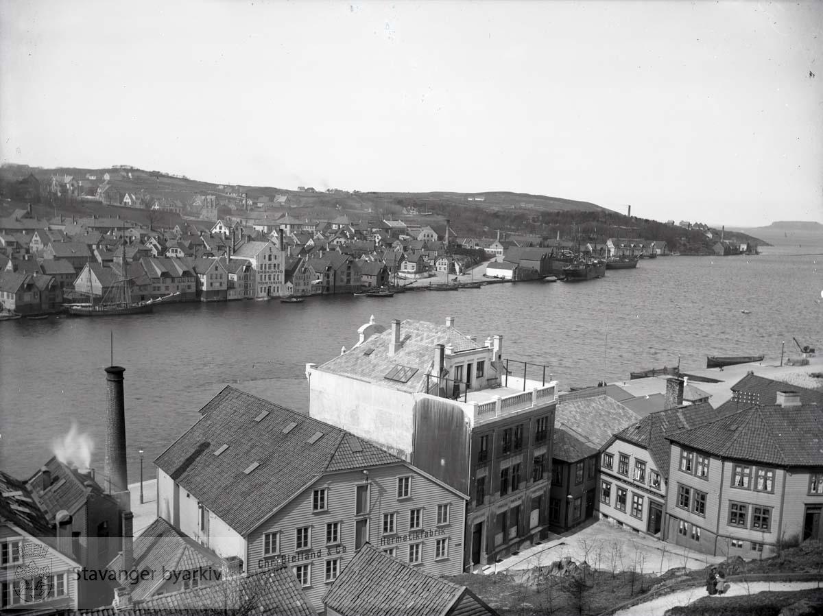 I forgrunnen: Skagen 36, 38, 40, 42 og 44. På vestre siden av Vågen ligger Stranden med husrekken til Nedre Strandgate mot sjøen. Sandviken til høyre. Skagen 36 var Chr. Bjellands første hermetikkfabrikk fra 1893. Fabrikk nr. 2 var Nedre Strandgate 67, den hvite murbygningen på andre siden av Vågen, bygget i 1897. Skagen 38 var Endre Berners kolonial- og skipshandel, bygget i mur i 1881 . Påbygget i 1901. Her stod tidligere et sjøhus som i 1860 markerte grensen for brannen på Holmen.