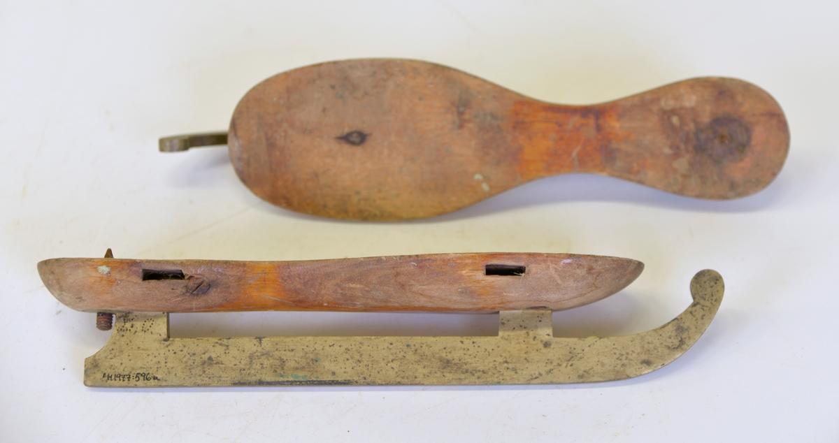 Skridskor med fotplatta av trä och medar av mässing. Medarna är uppsvängda framtill och flästade vid fotplattan med skenor