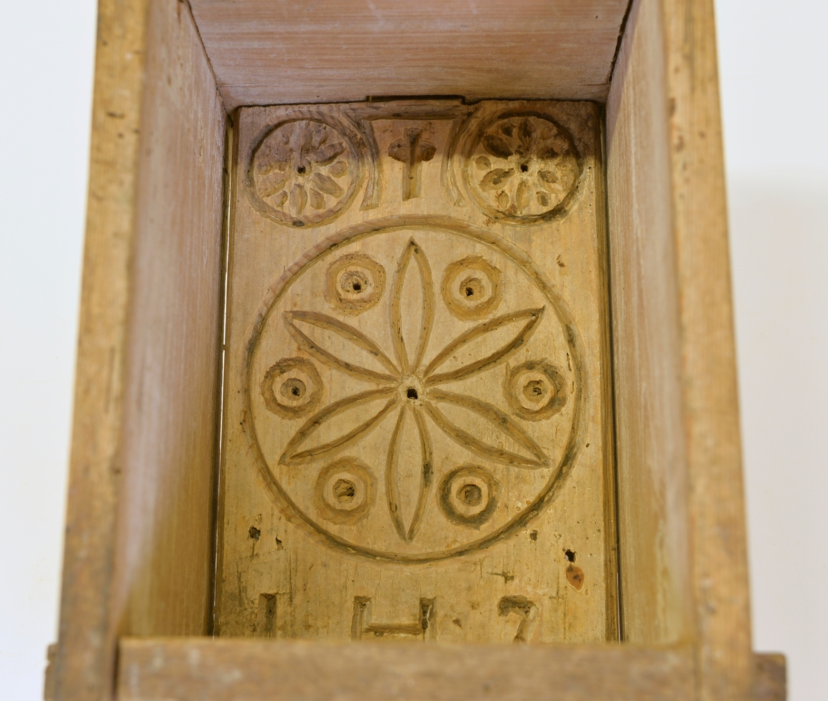 """Ostform med karvsnittsdekor i form av """"rosett"""", kors samt """"IHS"""". Kommer från Västergården, Maryd."""