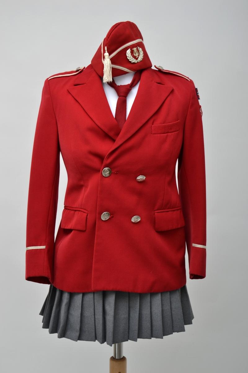 Korpsuniform bestående av jakke, skjorte, slips,to skjørt, hansker og lue. Jakken er dobbeltspent med 4 metallknapper, skulderklaffer og et felt med et smalt hvitt bånd på armene. Skjørtene er grå og plisserte og lukkes med knapp og trykknapper. Enkel hvit skjorte med rødt slips til. Uniformsluen er rød med hvite bånd og dusk i pannen. Et par hvite bomullshansker hører til. Jakken er i størrelse 10 år.