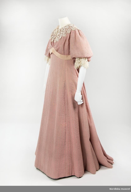 Klänning av rosavit yllecrepe i prinsessmodell med vid armbågslång  puffärm. Modellen avskuren under bysten och där markerad med band. Kjoldelen med längsgående sömmar något insvängd i midjehöjd. Sydd efter den norska reformdräktsförespråkaren Kristine Dahls mönster. Hennes modeller fanns till försäljning i Stockholm hos firma K.M. Lundberg vid Stureplan från 1896 och några år framåt. Klänningen som passade in i modet blev mycket populär under några år. /Ingrid Roos 2008-03-12