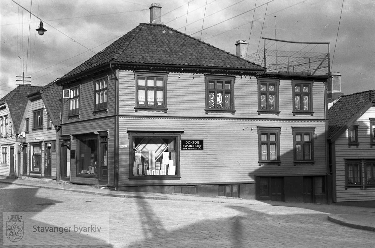 Doktor Kristian Gilje, står det på skiltet. Hans kontorlokaler var i Nr 75, nærmest bildet. Nr 77 og 79 videre innover. Veien ned til høyre er Bergene (Lars Hertervigs gate i dag).Huset helt til høyre er enten Bergene 6 eller Andasmauet 6..I nr. 77 holder barberer Helmer Hauan og damefrisør Aagot Hauan til.
