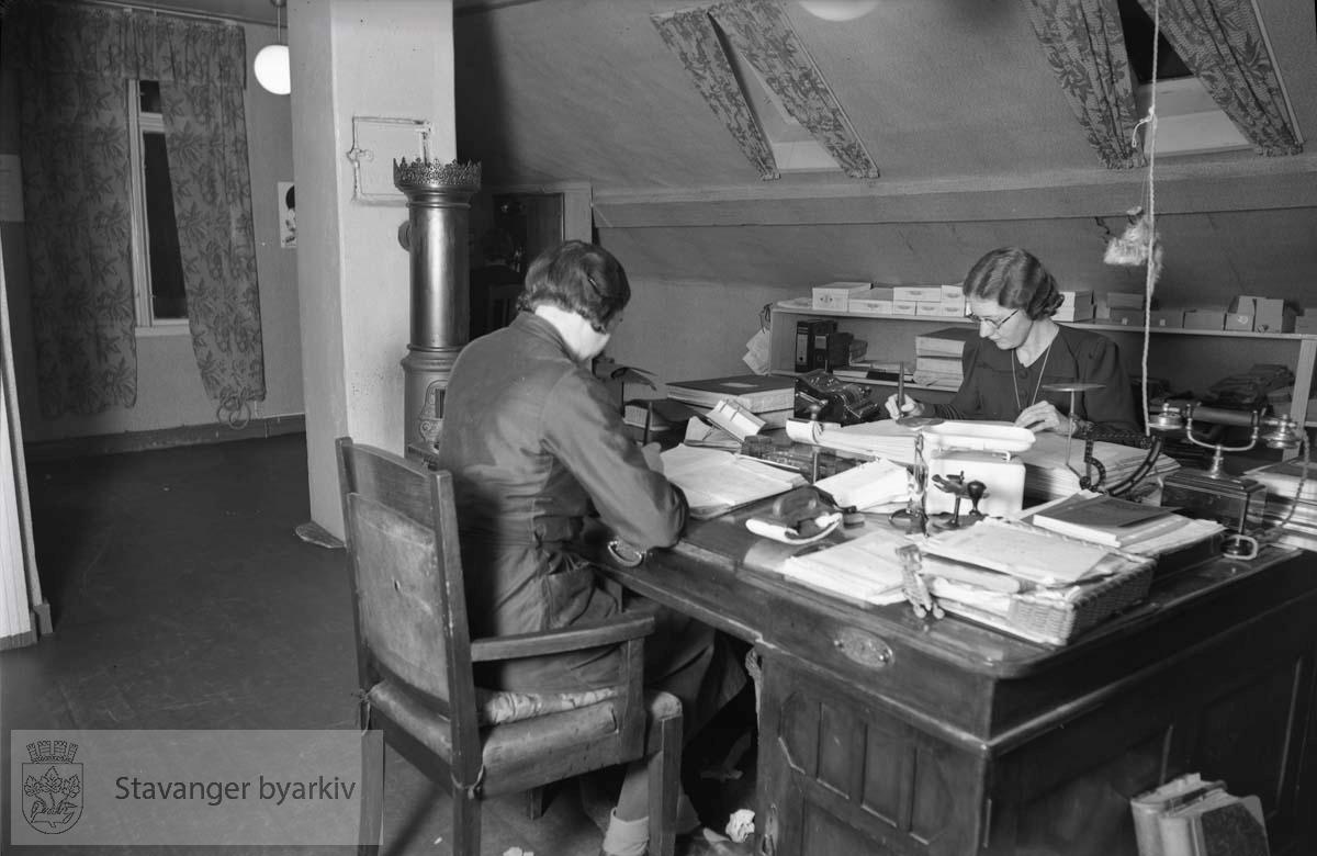 To kvinnelige sekretærer ved skrivebordet.