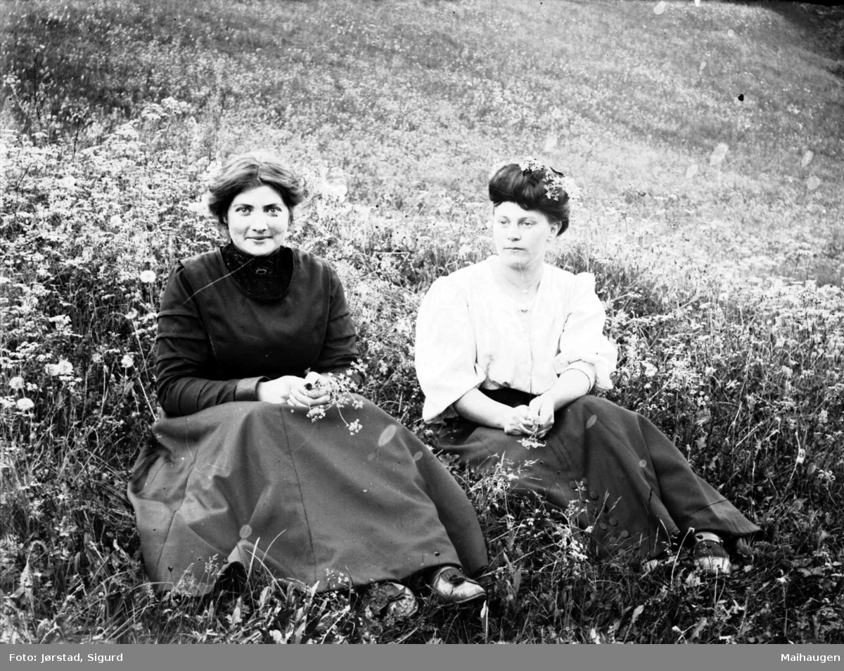 To unge kvinner sitter i en eng.