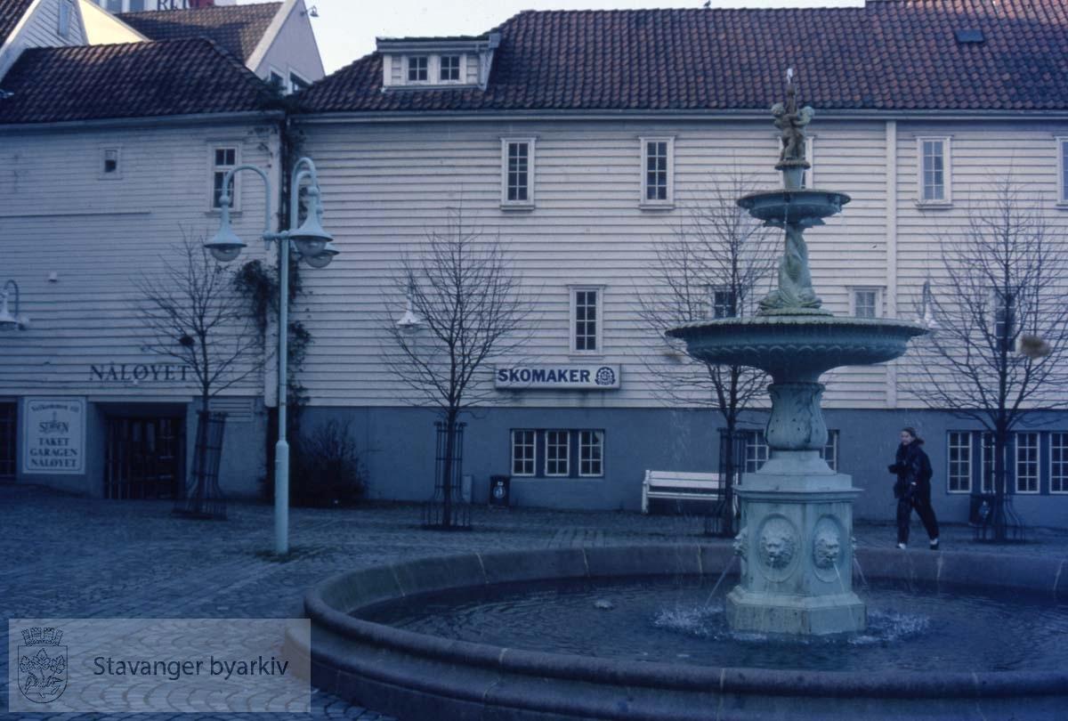 I forgrunnen: Fontenen som i sin tid erstattet Mortepumpen på torget (har også stått på Petri Plass og i Johannesparken).I bakgrunnen: utestedet Nåløyet samt en skomaker