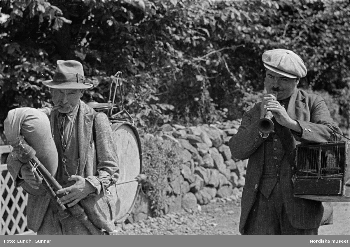 Två män spelar säckpipa och skalmeja samt bär på en bur med en papagoja, mannen med säckpipa har en trumma på ryggen, enligt uppgift från Bengt Edqvist 2018 kallas säckpipan zampogna och skalmejan ciaramella och papegojan drog ett slags lyckokort ur en kortlek, en kvinna håller ett spädbarn, en papegoja i en bur,