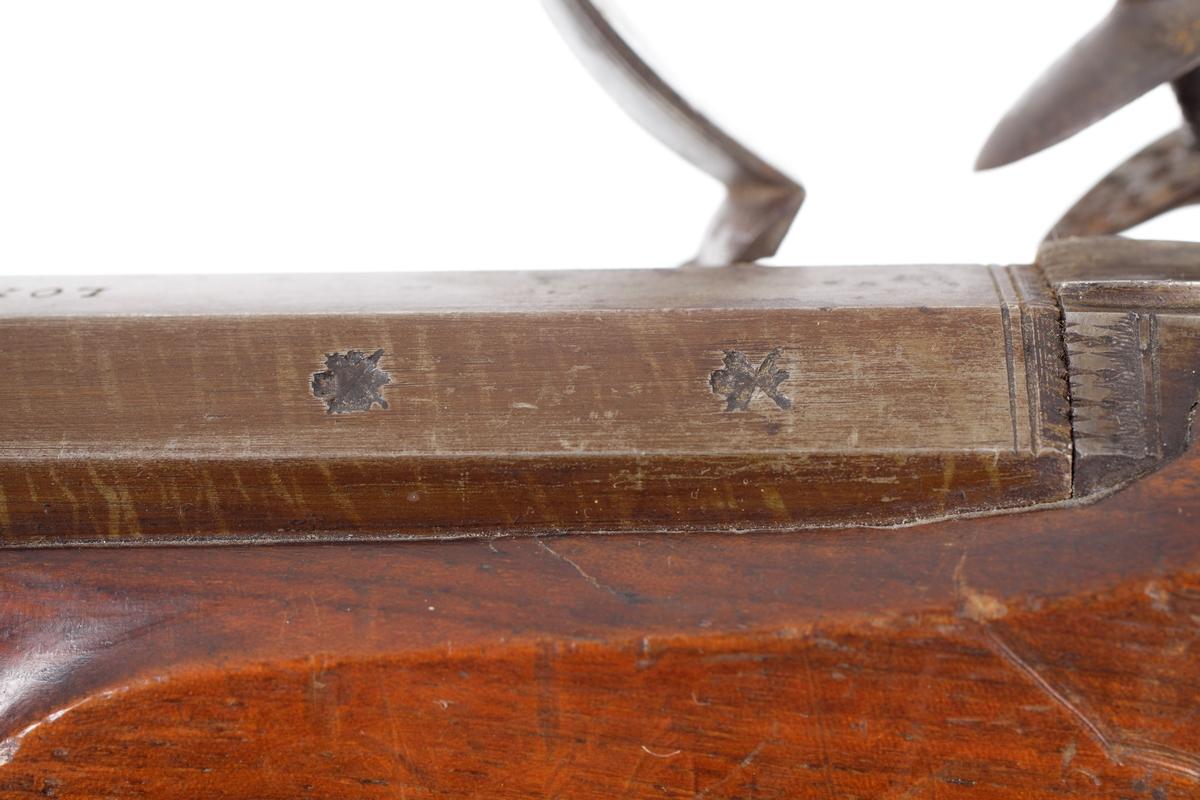 Jaktgevär försett med flintlås där framstocken går till en tredjedel av pipans längd. Näsbeslaget är tillverkat i horn och laddstocken sitter i tre rörkor fästade i pipans förstärkningsbalk. Kolvhalsen är smal och försedd med en nätskärning medan framstocken är slät. Även kolven är slät och odekorerad. Bakplåten är tillverkad av jrn och går en bit upp över kolvryggen där den avslutas med en spets. Pipan är damaskerad och brungjord. Den är rund i formen med en åttakantig avslutning. Vidare har den ett gropsikte vid svansskruven, samt ett korn strax bakom mynningen. Pipan är slätborrad med en innerdiameter på 15mm. Inskrivet i huvudkatalog, ej noterat.