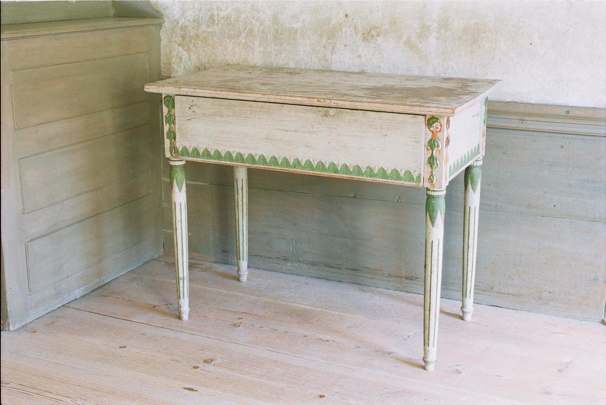 Mössbord i gustaviansk stil med låda, av furu målad i en gråvit färg. Rektangulär rak form, höga sarger med bladformad pastellagedekor i grönt. Svarvade bladhölstrade ben med kannelyrer, ifyllda med grönt.
