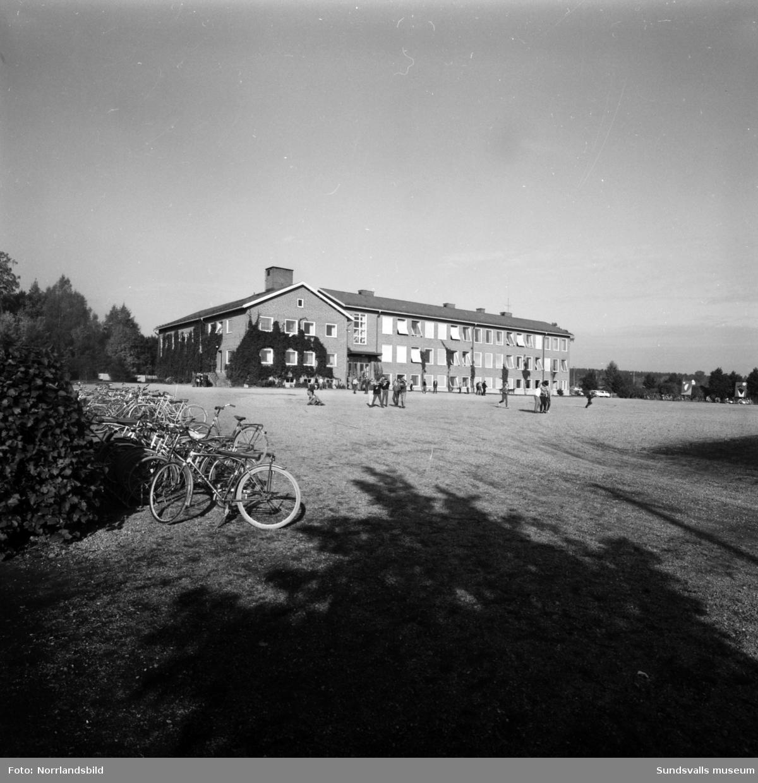 Vy över skolgården mot Fillans skola. På skolgården rör sig barn och en lång rad cyklar är parkerade i utkanten.