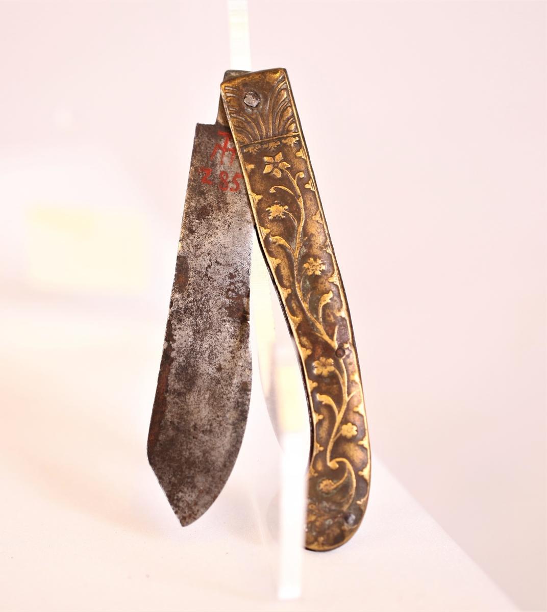 Bestikket består av to deler som kan festes sammen og ser da ut som en lukket foldekniv med smalt,litt kroket skaft. Tatt fra hverandre og foldet ut er den ene del kniv (a) og den andre gaffel (b). Kniven har spisst blad som er bredest ved spissen, gaflen er smal med to rette, lange tenner. Hver del har skaft av tynt jern på innsiden, på yttersiden støpt bronse med blomsterranke i relieff.