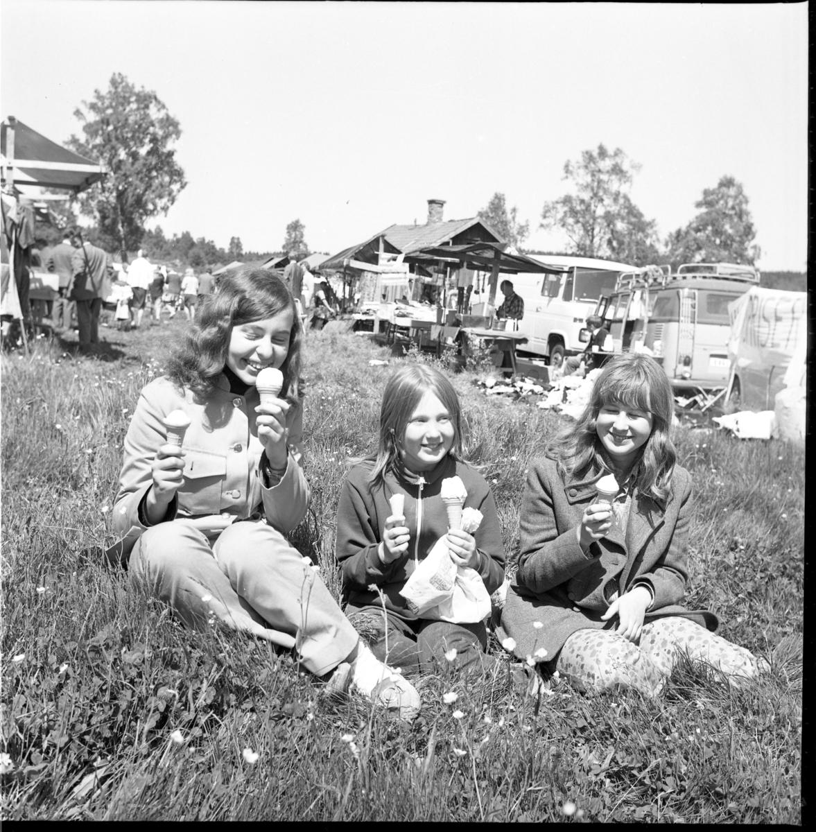 Tre glassätande flickor sitter i en slänt på Vireda marknad 1968. Från vänster: Ann-Britt Carlsson, Maria Ingesson och Lena Nyström.