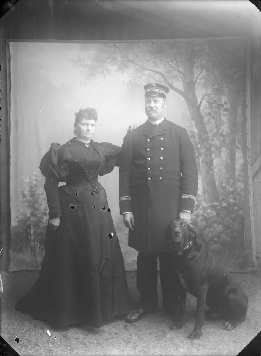 Jernbaneansatt mann (antatt stasjonsmester) med frue og hund