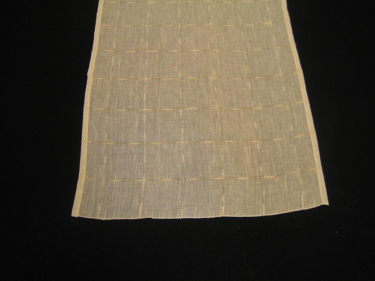 """Gardin med vit bomull i varp och halvblekt lin i inslag med rutor i effektgarn i bomull. Rutorna är 7,3 cm breda. Gardinen är monterad med ett vitt bomullstyg i överkanten. En lapp är fastsatt med texten: """"SKARABORGS LÄNS HEMSLÖJDSFÖRENING"""" på ena sidan och: """"Rutan, Bredd 110 cm, Bomull, lin, Material 47:-/m"""" på andra sidan. det finns också ett vävprov som är vävt med blekt lin i inslag."""