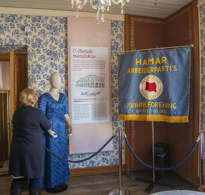 Fra utstillingen; en kjole sydd i disse lokalene på 1950-tallet av Frk. Jonine Grønsveen som drev systue her da, og Hamar Arbeiderpartis partifane som også ble sydd i disse lokalene.