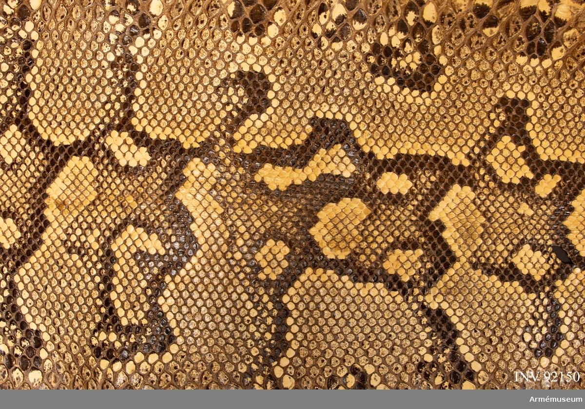 Inköpt på lokal marknad i samband med tjänstgöringen som FN-soldat i Kongo. Ormskinnet ska främst betraktas som ett uttryck för de svenska FN-soldaternas fascination inför exotiska djur och den vanligt förekommande företeelsen att söka sig till lokala marknader för att inhandla souvenirer av liknande slag. Föremålet kan ses som ett sätt att understryka erfarenheten om att ha varit på en mycket avlägsen, exotisk och samtidigt farlig plats.