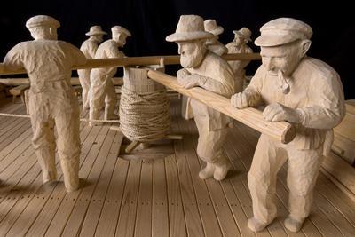 Modell av arbeidslag på spillflåte for buksering av tømmer på innsjø, skåret av treskjæreren Ragnar Nysæther.
