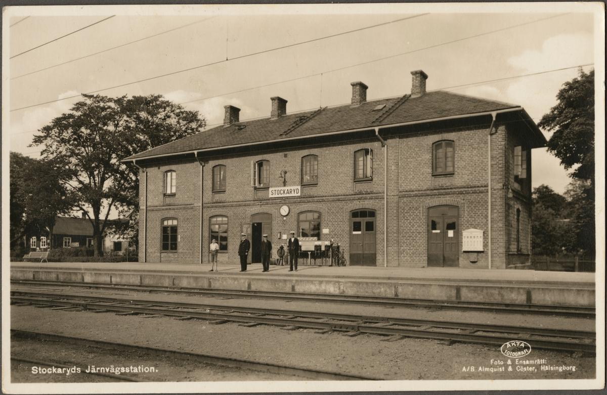Spårsida av station med personal i bild.