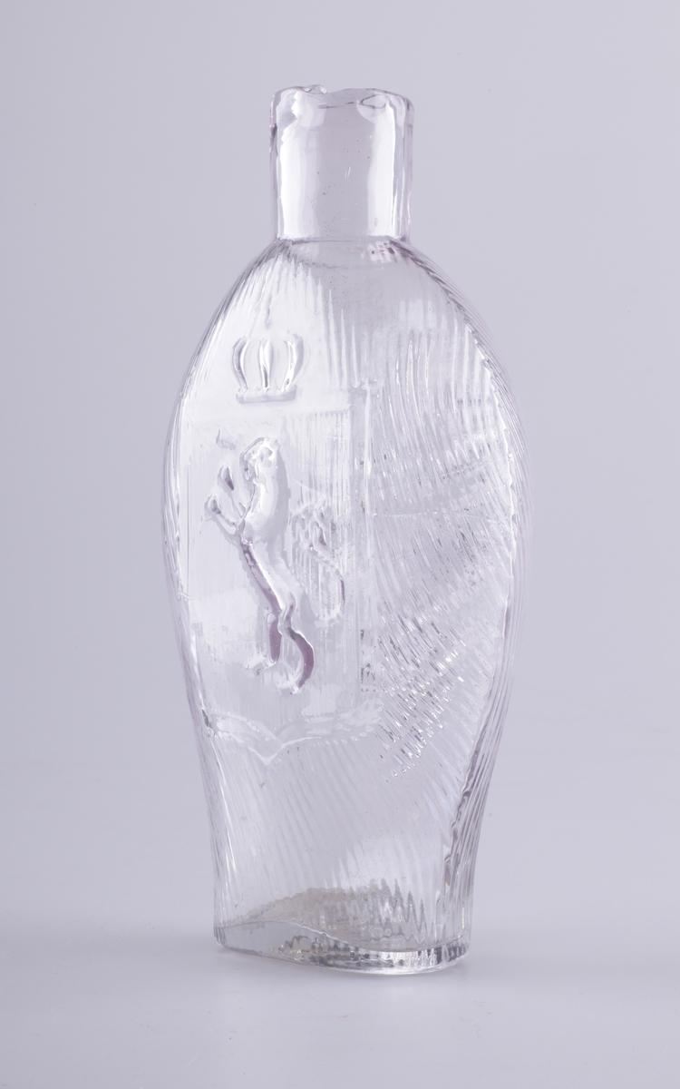 Lommeflaske blåst i form av noe rødlig glassmasse. Oval og noe flattrykket, dekorert med rifler, og på den ene siden den norske løve, på den andre vindrueklase.