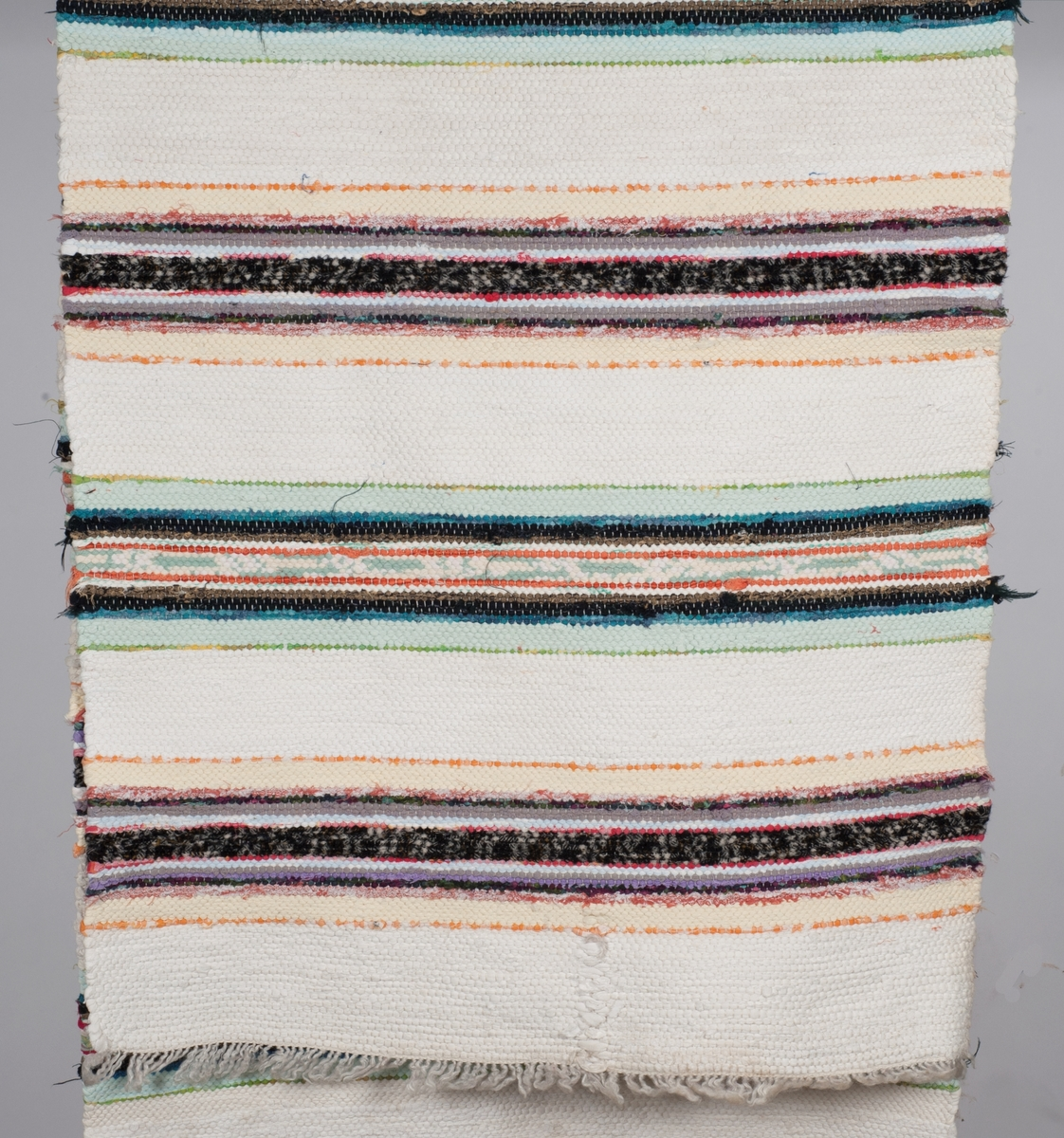 2e42d305 Fillerye med hvit renning og innslag med dekorative, alternerende border i  varme og kalde farger