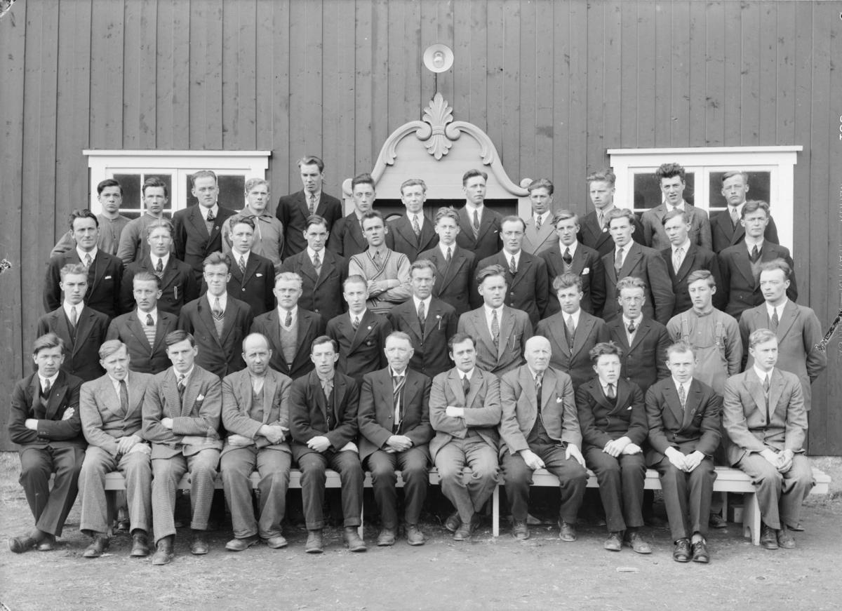 Elever og lærere ved Hjerleids Husflidsskole, Dovre. Lærer Ola Lillevik sitter midt i første rekke med Helge Hovrud og Ragnvald Einbu til høyre