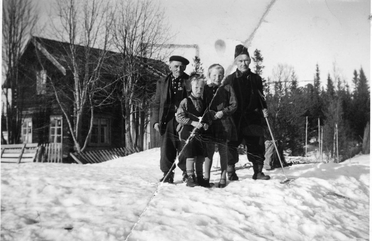 To barn og to menn foran hus, vinterstid