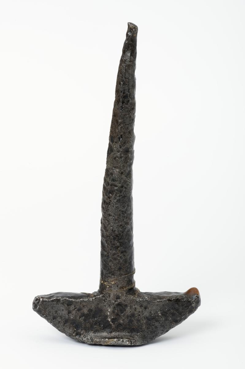 En av tre T-formete pjakser, haker eller nåler i jern brukt til å feste tømmer med kjetting til kjøreredskap, særlig lunneredskap.