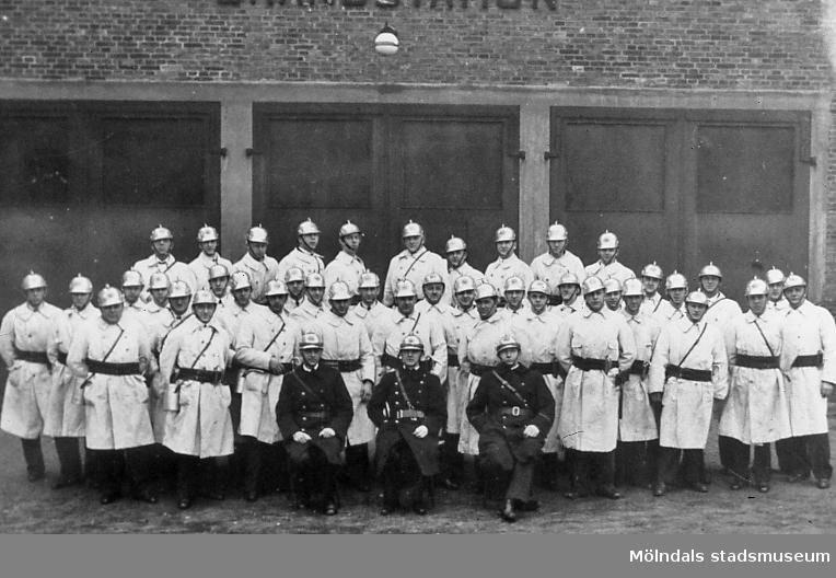 Grupporträtt av brandmän som är samlade utanför brandstationen, Kvarnbygatan 41, vid Gamla torget i Mölndals Kvarnby. Okänt årtal. Befälen från vänster: Åkerblom, John Carlström (chef) och Sommar.