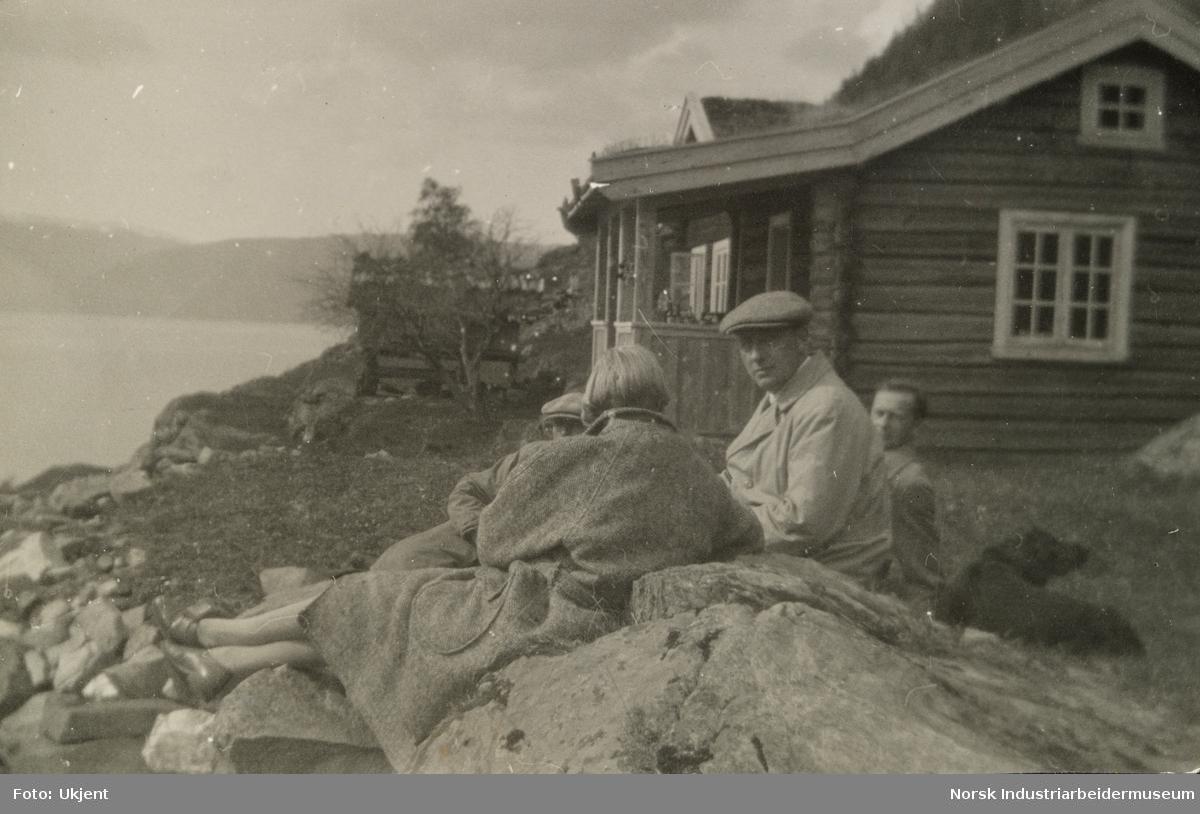 Mennesker sittet avslappet utendørs på stein på hyttetomt ved innsjø