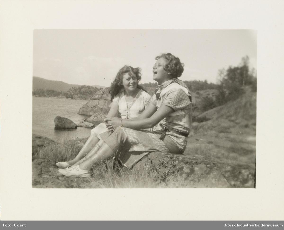 To unge kvinner sitter på fjell ved strand