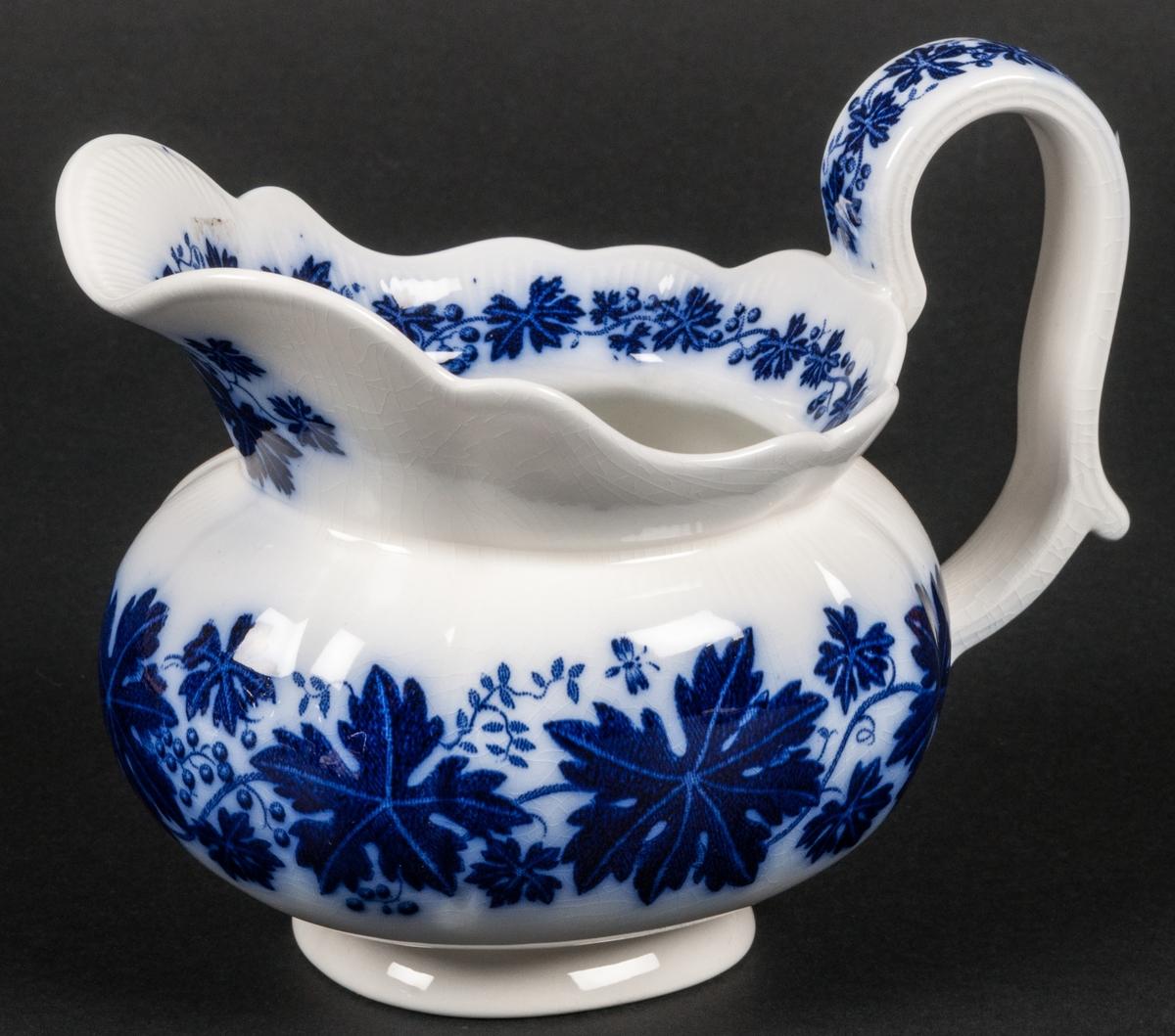 Såskanna, Modell AO. Vinranka blå. Vit botten med blå flytande dekor av vinrankor. Gravyrdekor under glasyen.
