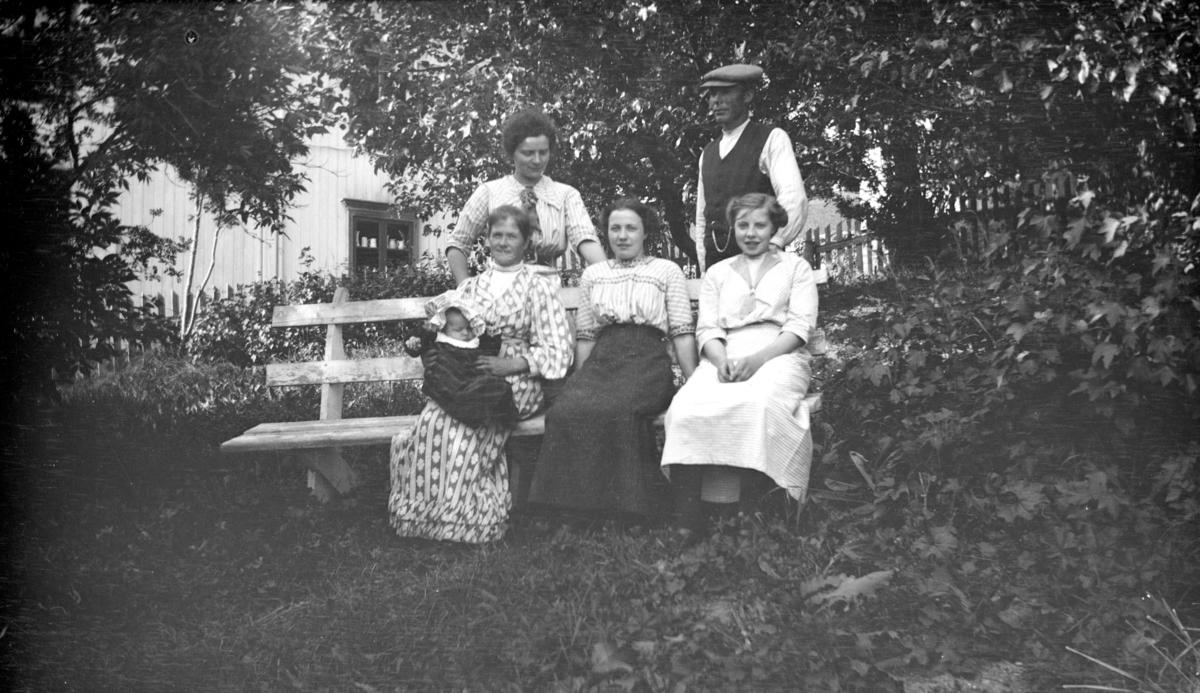 Seks personer i hagen, muligens på Linjordet i Østre Gausdal