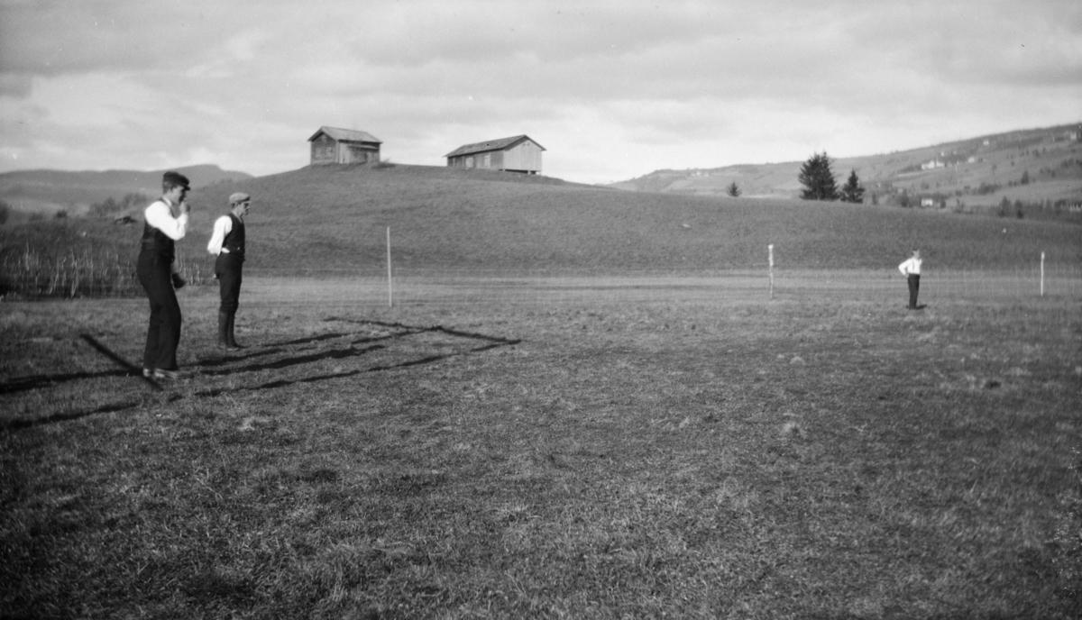 Tre menn på et jorde, gårdsbygninger i bakgrunnen