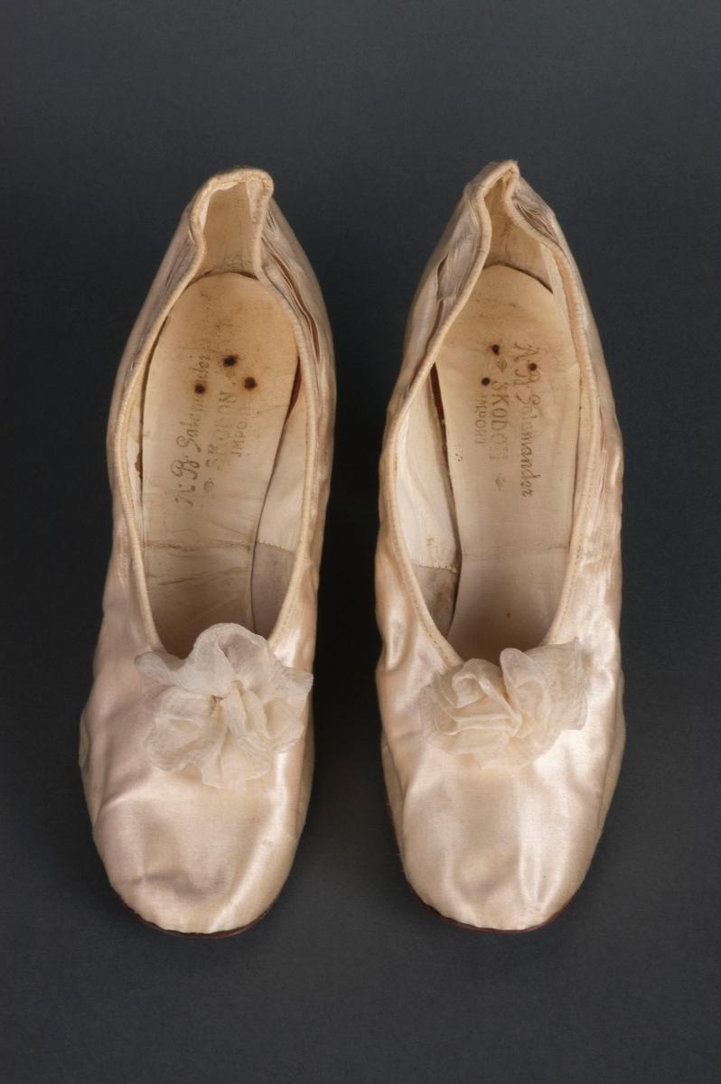 Hvite, ankelhøye pensko til kvinne. Liten hæl. Materiale muligens silke. Fargen er sannsynligvis noe falmet, bærer preg av alder. Noe skrukkete i formen, samt noen rifter i kantene ved ankel.