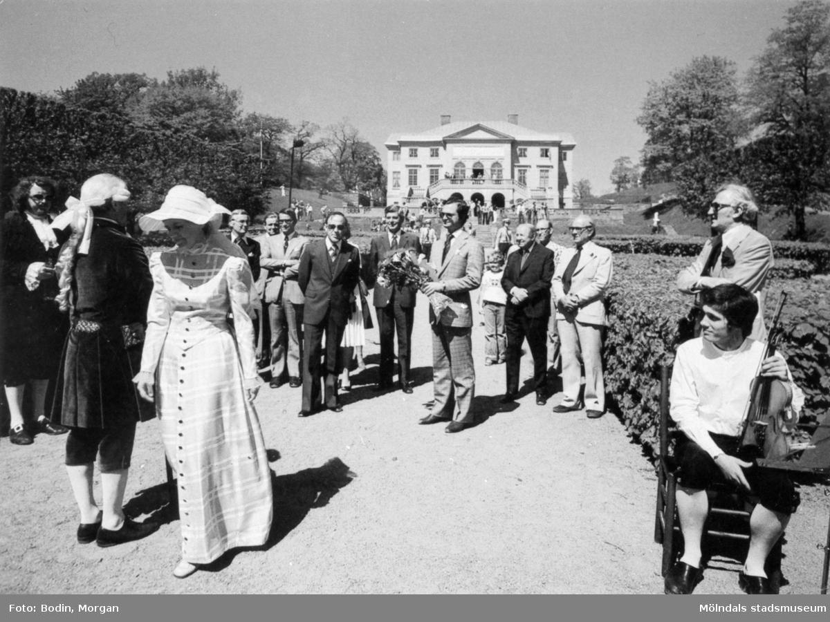 Kungabesök på Gunnebo slott, år 1977. I mitten ses Kung Carl  XVI Gustaf hållandes en  blombukett. Längst till vänster Jan Ivar Blixt. Till vänster om kungen står rektor Åke Baaz och landshövdingen Erik Huss. Längst åt höger står fil.dr. Nils Dahlbeck och chefrededaktör Jon E. Lisshammar. mannen som sitter på en stol längst ut till höger är Ivan Hagberg. Vykort, förlag: Mölndals Kommun.