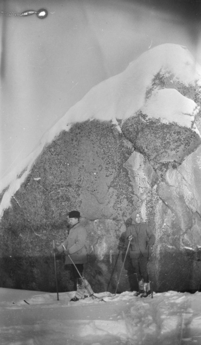 To skiløpere ved siden av en stor stein.