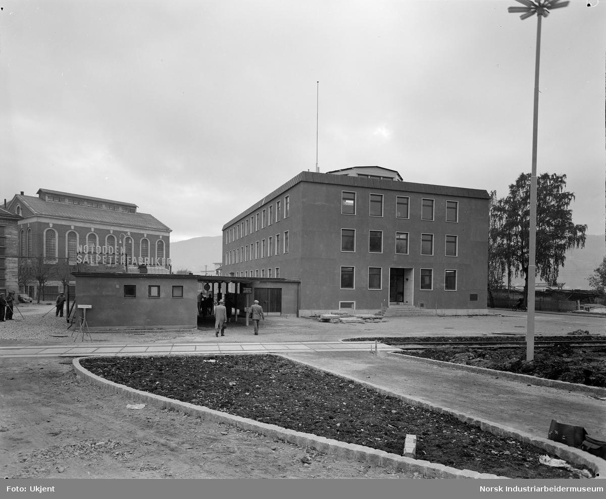 Arbeid utenfor portvakta som er arbeidernes inngang til fabrikken. Mennesker på vei gjennom portvakta.  Kontorbygget i Hydroparken til høyre (bygg 1, oppført 1955).