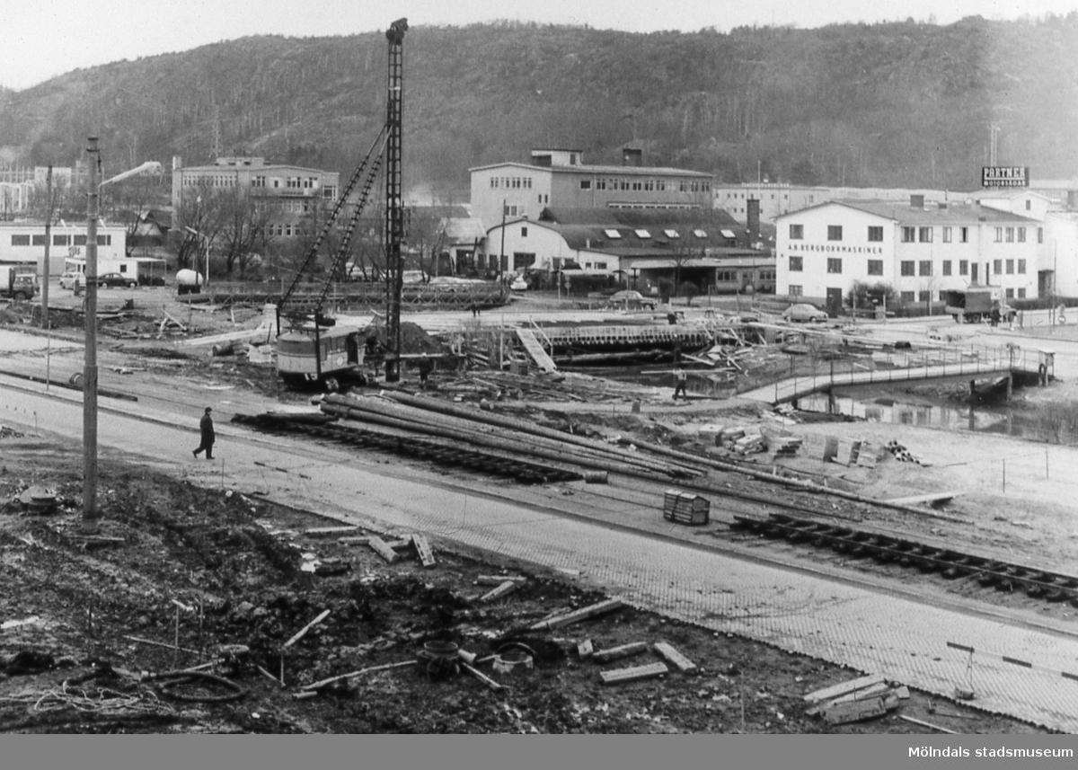 Lackarebäck i Mölndal, troligen på 1960-talet. Lackarebäcksbro byggs ny när E6 skulle passera Mölndal. I förgrunden ses Göteborgsvägen och spårvägen. På andra sidan Mölndalsån ses industribebyggelse i Lackarebäcks industriområde. AF 10:17.