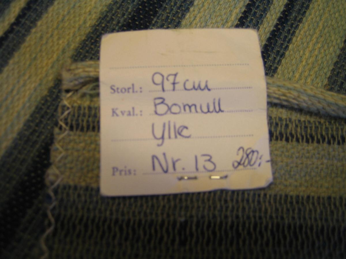 """Ett stadigt möbeltyg i tuskaft. Tyget är randigt med en smala och breda ränder i blått, vitt och grått.  Varpen är grått bomullsgarn. Inslaget är ull.   En lapp är fastsatt med texten: SKARABORG LÄNS HEMSLÖJDSFÖRENING SKÖVDE-LIDKÖPING"""" på ena sidan och """" Storl.: 97 cm Kval.: Bomull, Ylle Pris: Nr. 13, 280:-"""" på andra sidan."""