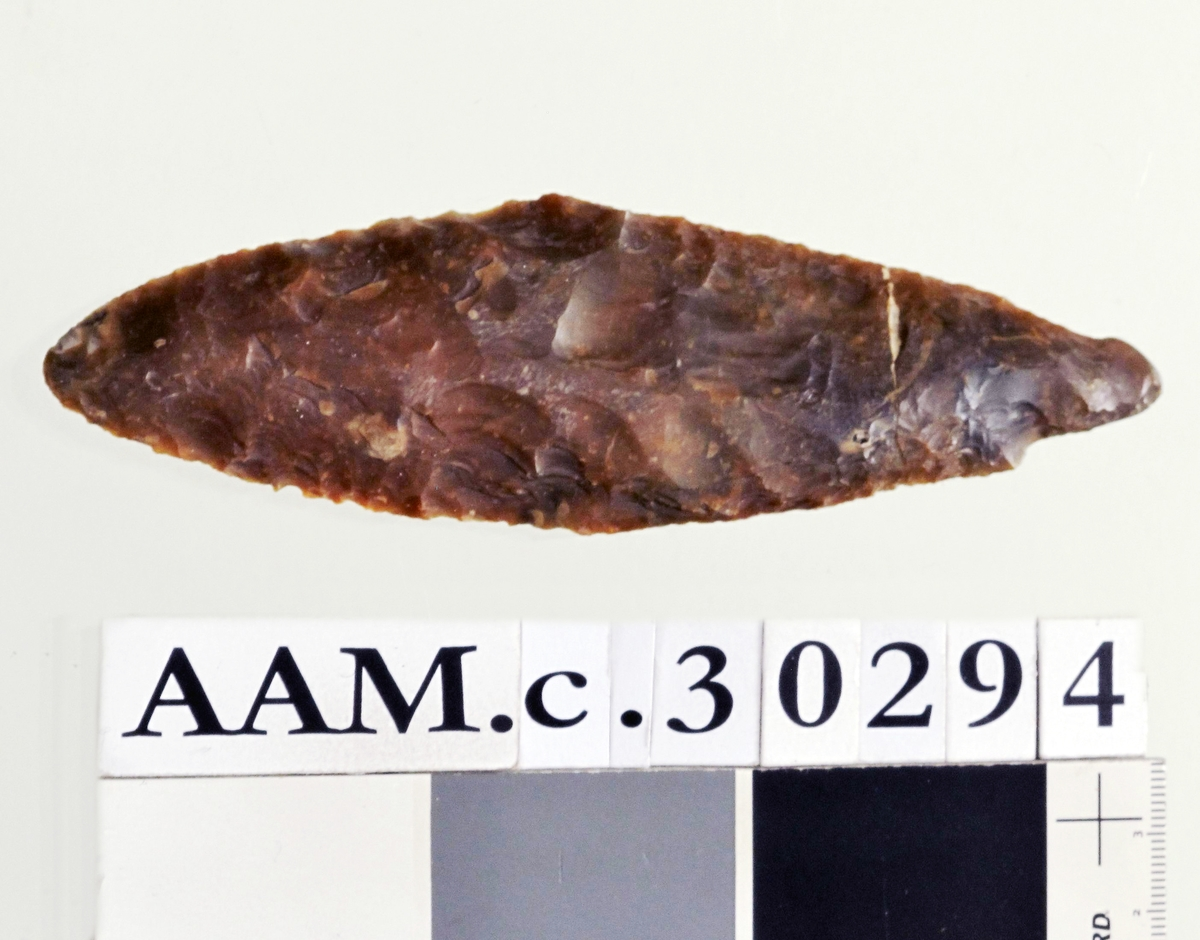 Dolk av rødbrun flint, av typen H. Gjessing: Rogalands Stenalder, fig. 197, men mindre slank og med største bredde omtrent midt på stykket. Slipespor på den ene siden. Det erderfor mulig at et slipt redskap (øks) har utgjort emne Ganske pent hugget og godt bevart.