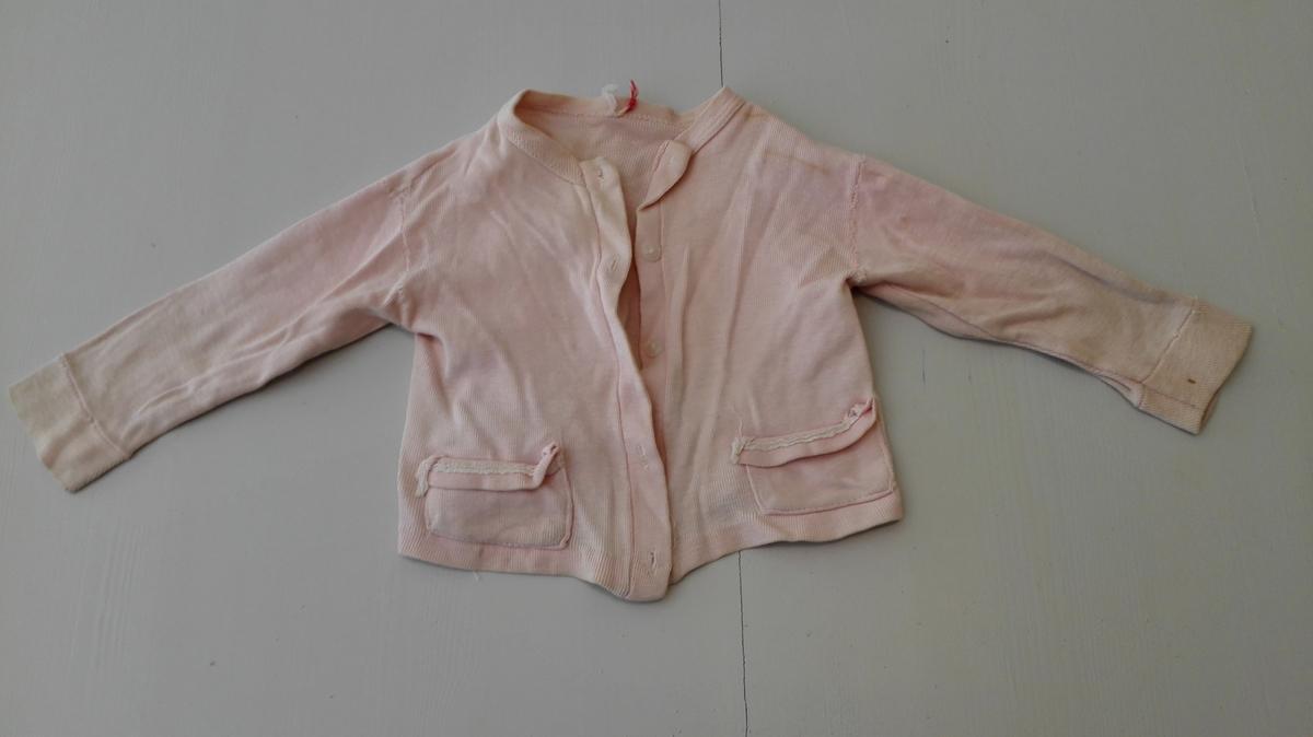 Form: Forknappa , rett modell med lommar. Langt erme. Rosa spebarnplagg vart mykje brukt til jentebarn på denne tida.