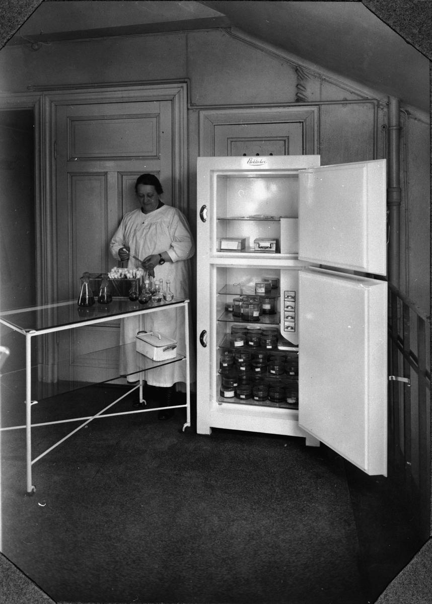 """Electrolux kylskåp typ D i """"Statsmedecinska Anstaltens Bakteriologiska Avdelning"""". Kylskåpet användes för förvaring av vaccin. Genom kontinuerlig drift erhålles i nedre avd. en temperatur av -2 grader Celsius. >> Kvinnan hämtar vaccin??"""