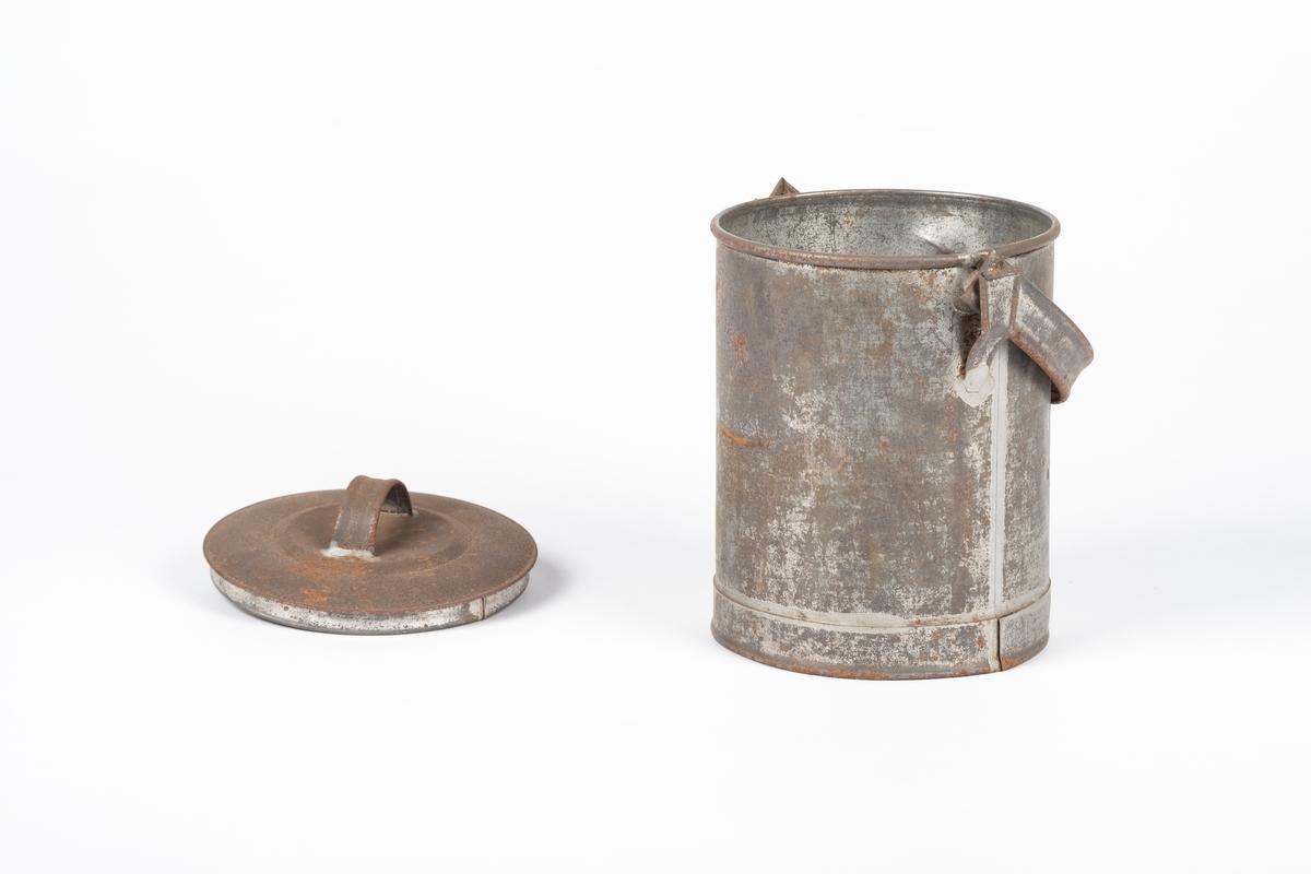 Sylinderformet blikkspann med hank og lokk. Sylinderen består av en plate hvor endene er føyd sammen. Langs skjøten mellom sylinderen og bunnen går det en kant som spannet står på. Hanken er festet i to ører og kan svinges over lokket. Lokket har et lite håndtak i topp.
