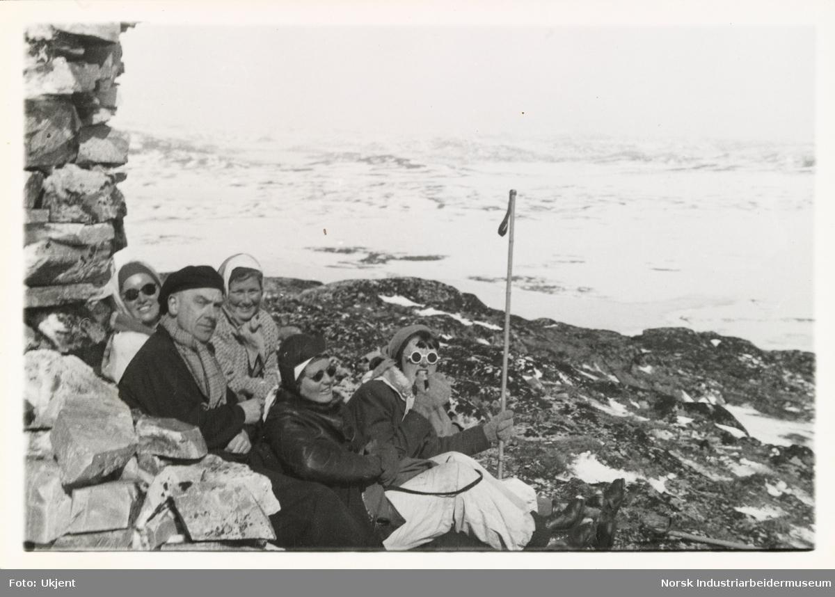 En mann og fire kvinner sitter ved varde i turantrekk på fjellet