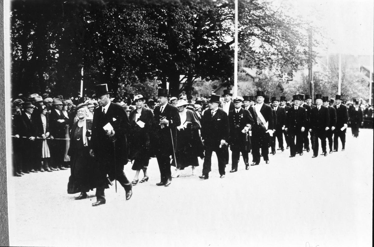 Riksdagens 500-årsjubileum firas i Arboga. Avmarch till Heliga Trefaldighets kyrka. Herrar i stormhattar promenerar på Järntorget. Några kvinnor syns också. Publiken står bakom avspärrning. (Arbogautställningen pågår samtidigt)