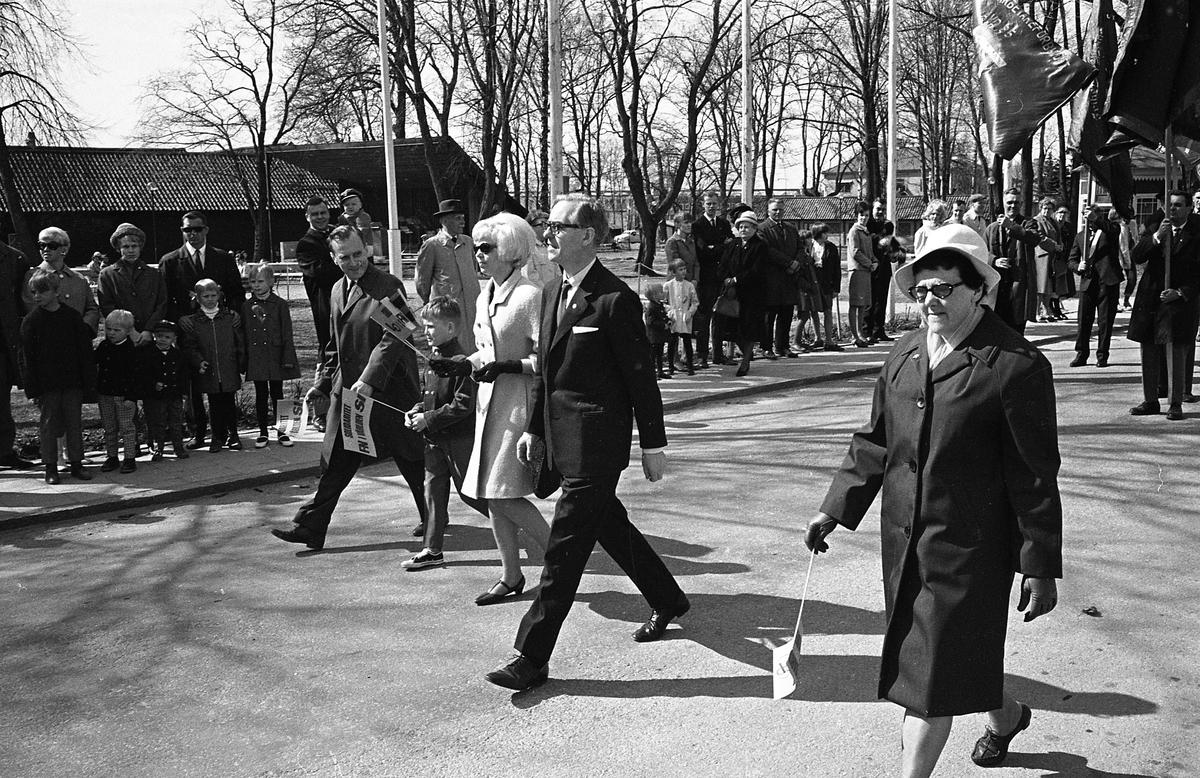 1a majtåg. Demonstration Längst till vänster går Bertil Karlsson (ordförande i stadsfullmäktige) och hans son, Berit Oscarsson (ungdomstalare från Sveriges Socialdemokratiska Ungdomsförbund), Åke Zetterberg (pastor och ordförande i Broderskapsrörelsen) samt Anna-Lisa Isaksson (orförande i Fackens CentralOrganisation) Människor med fanor och vimplar. Publik efter vägen. Olof Ahllöfs park i bakgrunden. Olof Ahllöfs park, med scenen, syns i bakgrunden