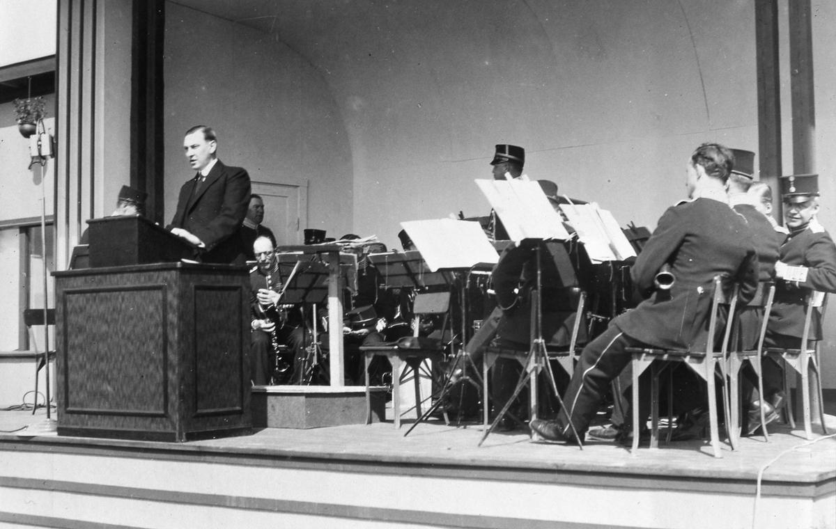 Borgmästare Wilhelm Wester invigningstalar på Arbogautställningen. Bakom honom, på scenen, sitter en uniformsklädd blåsorkester.
