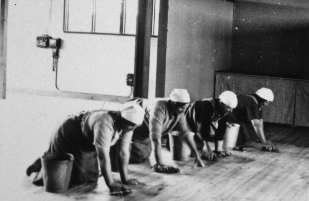 Arbogautställningen ska snart öppna! Dags att städa. Fyra kvinnor knäskurar golvet i stora utställningshallen. Var och en har en hink med vatten och en trasa.